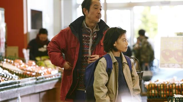 Ein Mann und ein junge stehen in einem Laden. Der Mann steckt sich unauffällig etwas in die Jackentasche