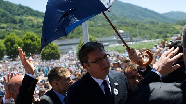 Serbiens Ministerpräsident Alexandar Vucic wird mit einem Schirm vor Angriffen geschützt.
