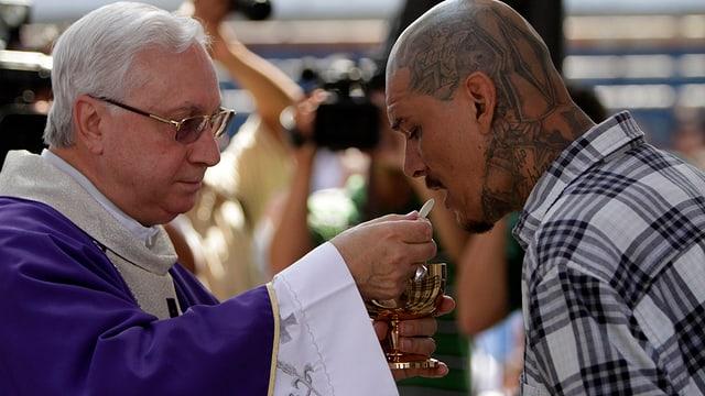 Ein Bischof überreicht einem tätowierten Bandenmitglied eine Hostie.