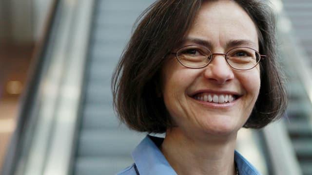 Fehlmann trägt eine Brille und ein blaues Oberteil, hat braune Haare und brauen Augen. Sie steht vor einer Rolltreppe.
