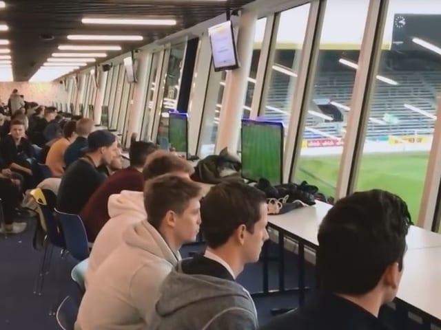 Eine Gruppe junger Männer spielt das Computerspiel FIFA an einem langen Tisch am Fenster mit Blick auf den Fussballplatz des FC Luzern.