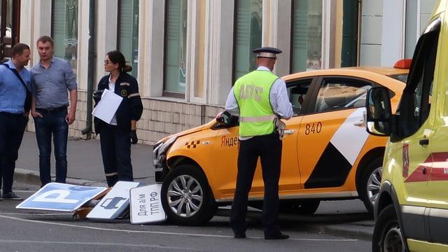 Ein Polizist steht beim Taxi