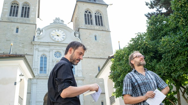 Peter Conradin Zumthor und Gabriel Schneider lauschen auf dem Platz vor der Luzerner Hofkirche dem Klang der Glocken.