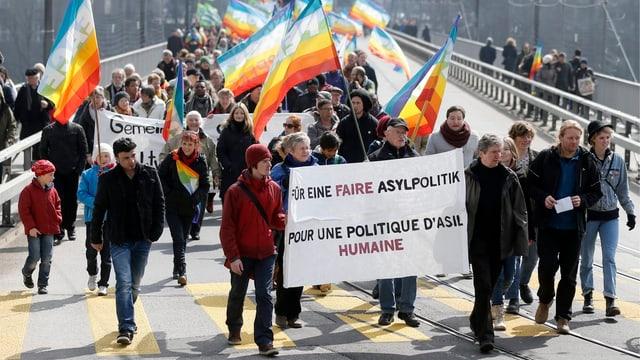 Viele Menschen auf der Strasse mit Transparenten und Regenbogen-Fahnen.