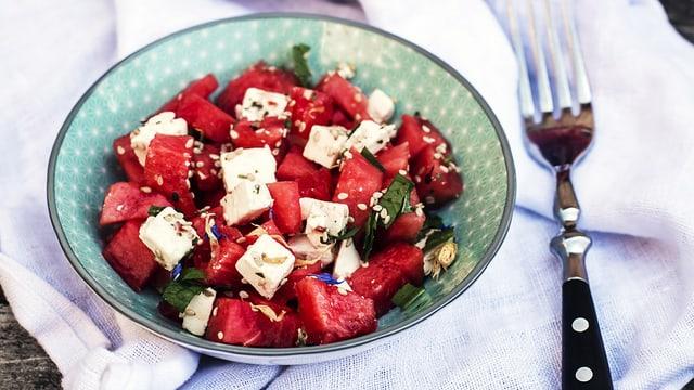 Ein Teller mit Stücke von Wassermelone und Fetakäse, zu einem Salat angerichtet.