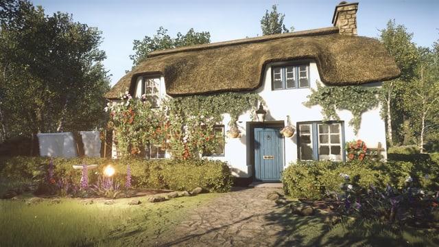 Ein weisses Haus mit Strohdach, mit Blumen überwachsen.