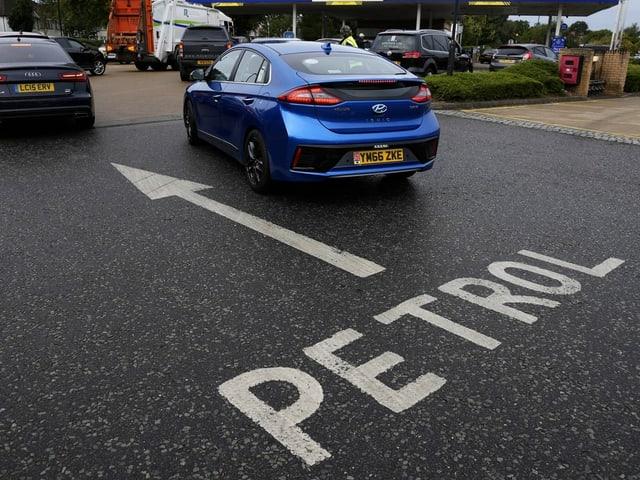 Ein Pfeil zeigt zur Tankstelle, daneben wartende Autos.