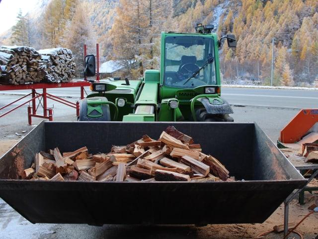 Transporter mit einerSchaufel voll Holzscheite.