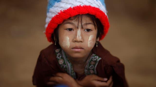 Ein Kind mit bunter Mütze blickt traurig.