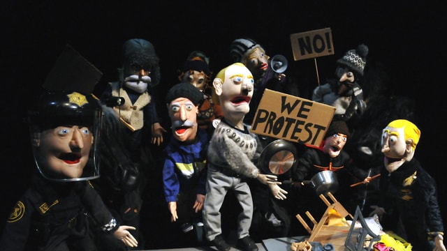 Eine Szene mit Demonstranten und Polizisten in einem Puppentheater
