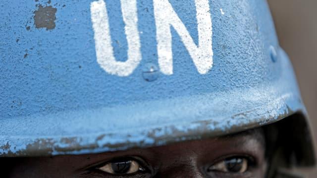 Blauer Helm mit Aufschrift «UN», Augen.