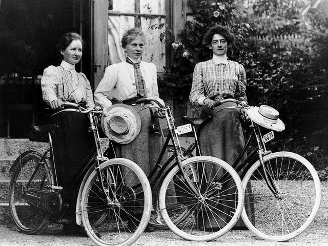 Schwarzweissbild: Drei Frauen mit Fahrrädern.