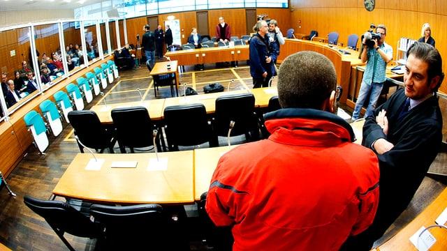 Der angeklagte ehemalige deutsche Söldner der IS-Terrormiliz Kreshnik B. in roter Jacke steht im Oberlandesgericht Frankfurt mit dem Rücken zum Forografen. Neben ihm steht sein Anwalt.