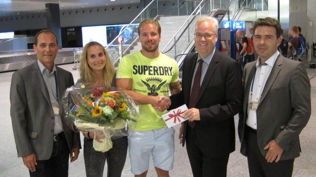 Ein Flughafenangesteller schüttelt einem jungen Mann die Hand, seine Partnerin hält einen Blumenstrauss.