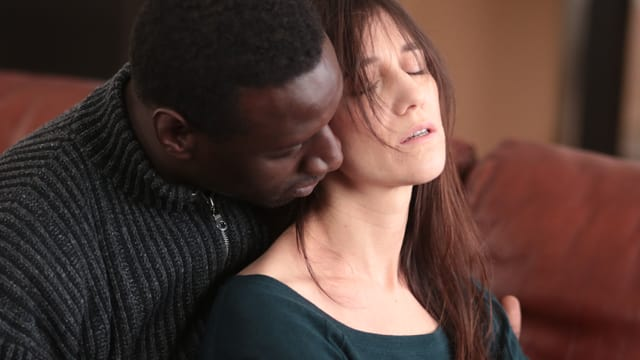 Ein schwarze Manner hält eine Frau an den Armen. Es ist eine innige Situation.