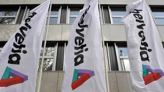 Flaggen mit Helvetia-Logo vor einem Gebäude.