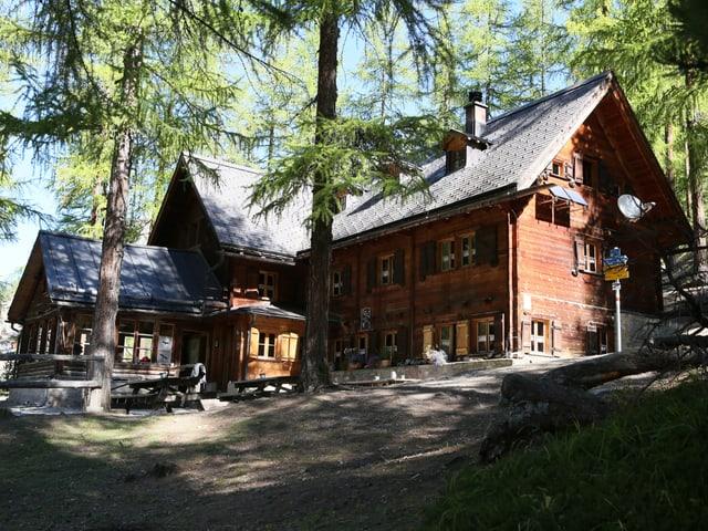 Die Cluozza-Hütte mitten im Wald.
