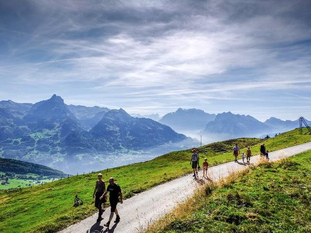 Auf dem Bild sind Wanderer zu sehen, oberhalb Amden im Kanton St. Gallen.