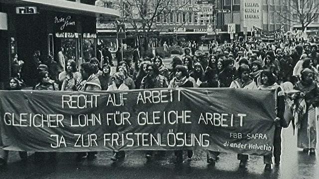Demonstration. Strasse voll mit Menschen. Vorne tragen sie ein Plakat auf dem steht: Recht auf Arbeit! Gleicher Lohn für gleiche Arbeit. Ja zur Fristenlösung. Das Foto ist schwarzweiss.