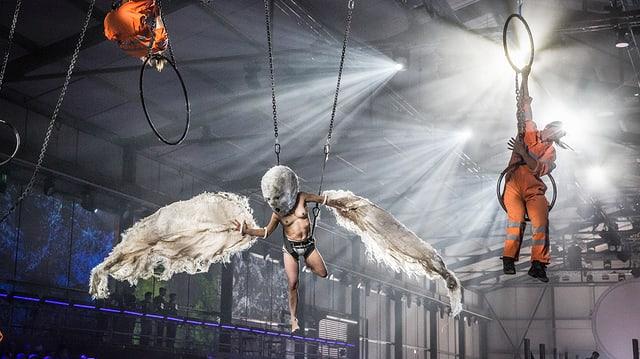 Menschen hängen von der Decke, einer hat Flügel und ist obenherum nackt.