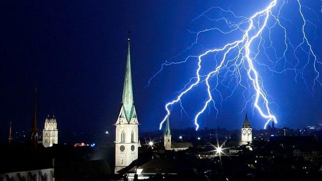 Vier Zürcher Kirchtürme bei Nacht, dahinter geht ein Blitz nieder