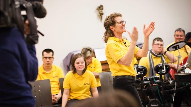 Christina Frei-Hutter klatscht vor ihren Sängerinnen und Sänger in die Hände.