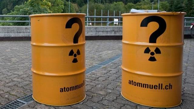 zwei gelbe Fässer mit einem Fragezeichen und dem Zeichen für Radioaktivität