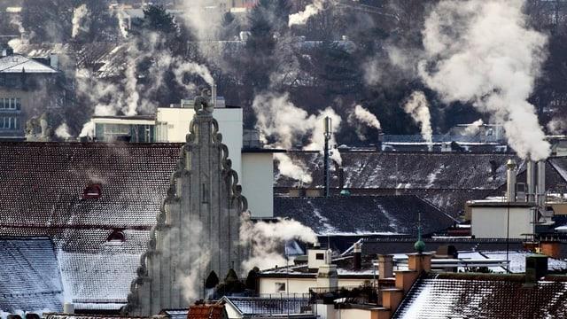 Leicht Schneebedeckte Dächer und rauchende Schornsteine.