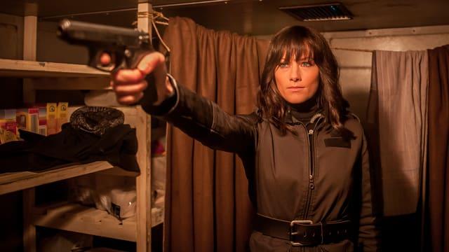 Helene Fischer mit brauner Perücke zielt mit einer Waffe nach links.