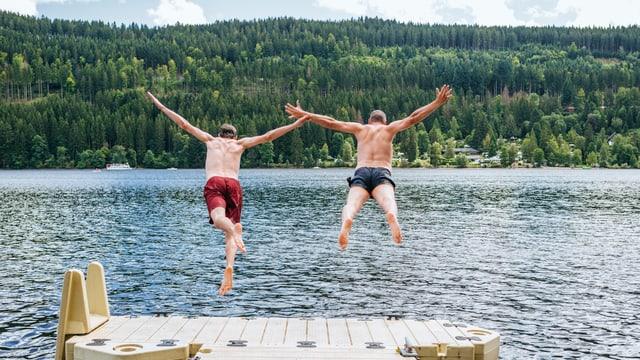 Zwei Männer in Badehose springen am Ende eines Piers gemeinsam in den See.