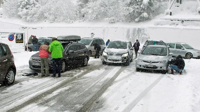 Auf der Hauptstrasse von Göschenen nach Andermatt herrscht derzeit Schneekettenpflicht. Deshalb werden auf dem Parkplatz die Ketten montiert. (Keystone)