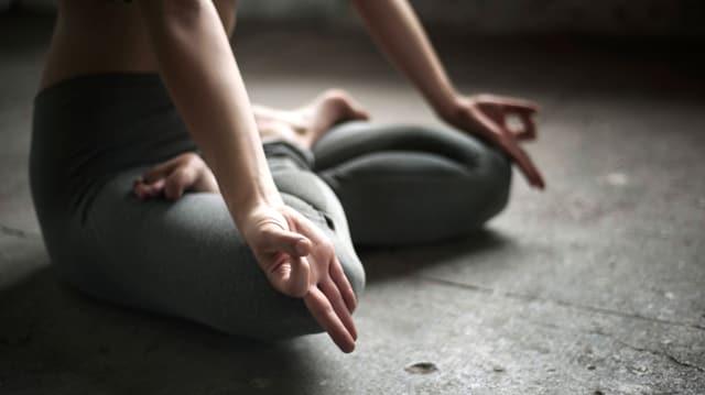 Eine frau sitzt im Schneidersitz auf dem Boden, die Hände links und rechts auf die Knie gelegt.