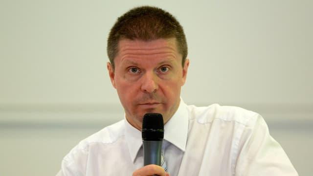 Purtret da Martin Bäumle cun in microfon.