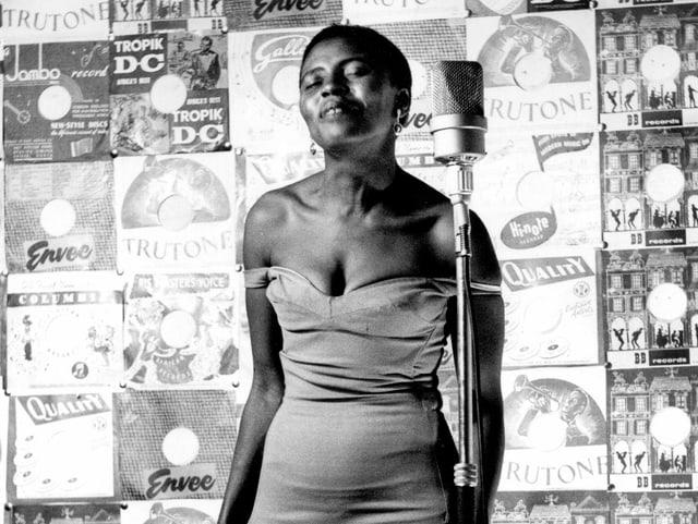 Miriam Makeba in einer s/w-Aufnahme vor dem Mikrofon in einem eleganten Kleid und ganz kurzen Haaren.