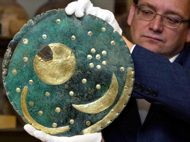 Ein Mann mit weissen Handschuhen hält eine türkisfarbene Scheibe mit goldener Sonne, Mond und Sterne