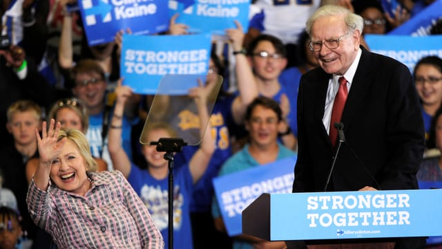 Warren Buffett steht an einem Rednerpult; Hillary Clinton daneben winkt.