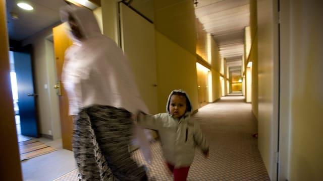 Verschleierte Frau mit Kind an der Hand geht durch Hotelflur