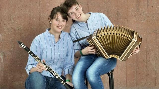 Zwei Mädchen im Sennenhemd mit Klarinette und Schwyzerörgeli.
