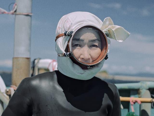 Eine Frau ist dabei zu tauchen, sie trägt einen Neoprenanzug und ein Kopftuch.