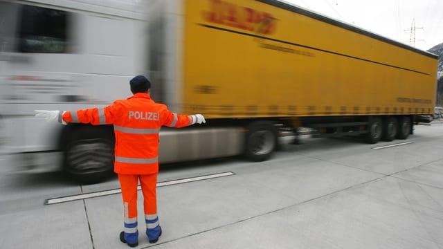 Ein Polizist weist einen Lastwagen beim Schwerverkehrszentrum Erstfeld ein.