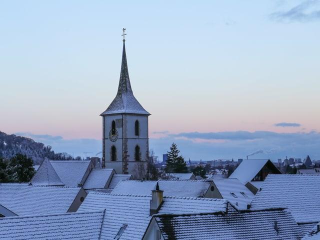 Blick über weisse Dächer auf eine Kirche.