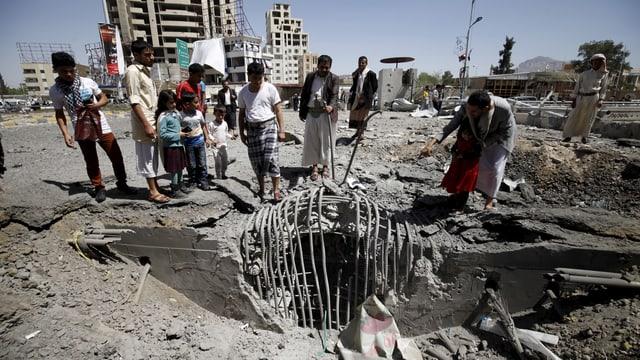 Menschen stehen um dein Einschlagsort einer Bombe in der jemenitischen Hauptstadt Sanaa.