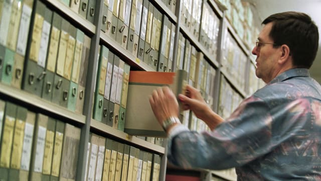 Ein Steuerinspektor zieht eine Akte aus dem Regal