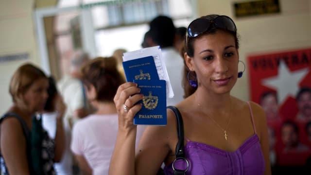 Eine Kubanerin hält lächelnd zwei Reisepässe in die Höhe.