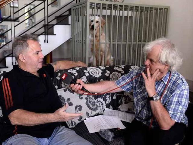 Zwei Männer sitzen auf einem Sofa. Einer hält dem anderen ein Mikrofon hin.