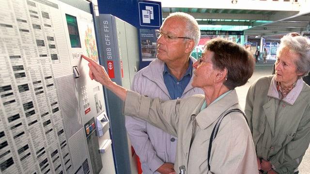 Drei ältere Personen bedienen zusammen einen Billett-Automat.