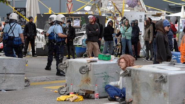 Polizisten in Montur, Besetzer und umgekippte Abfallcontainer
