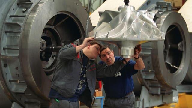 Zwei Arbeiter prüfen grosse Bauteile in einer Fabrikhalle der ABB.