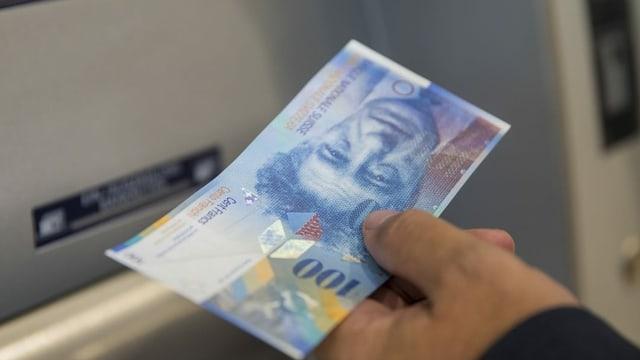 Um che retira 100 francs dad in bancomat.