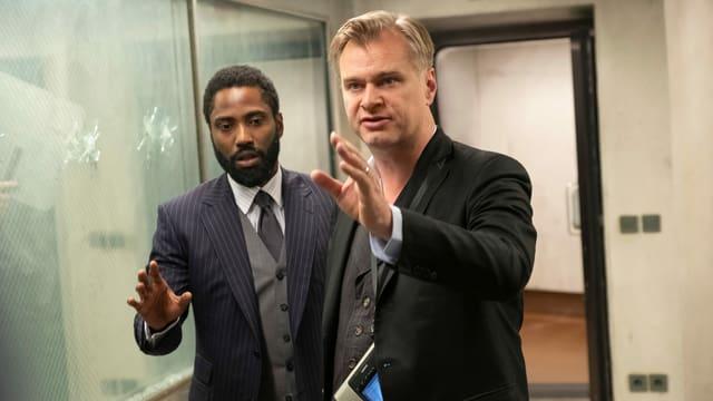 Christopher Nolan unterhält sich auf dem Set mit John David Washington.